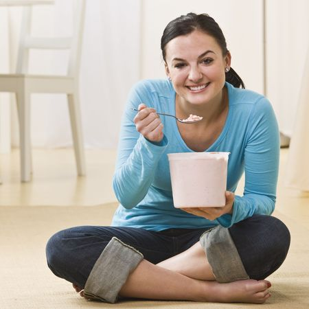 woman sitting floor: Attractive woman sitting on floor with crossed legs and eating ice cream. Square