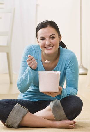 eating ice cream: A young woman is sitting on the floor and eating ice cream out of a tub.  She is smiling at the camera.  Vertically framed shot.