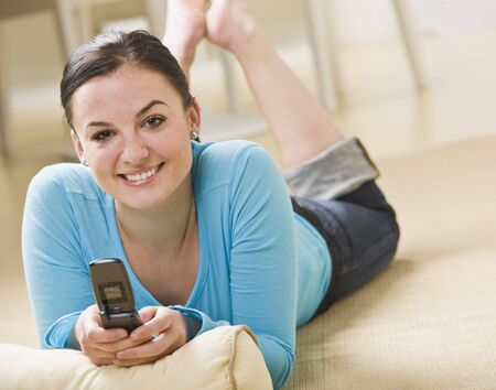 midlife: A woman is laying on her stomach and holding a cell phone.  She is smiling at the camera.  Horizontally framed shot. Stock Photo