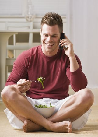 A man is talking on a cell phone and eating a salad.  He is smiling and looking away from the camera.  Vertically framed shot. Banco de Imagens