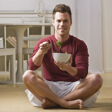 midlife: Attractive man smiling at camera, sitting in lotus and eating salad. Square. Stock Photo