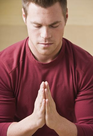 Attractive male praying with eyes closed and palms together. Vertical 版權商用圖片