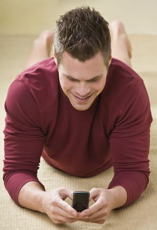 midlife: A man is holding a cell phone and is texting.  He is smiling and looking away from the camera.  Vertically framed shot.