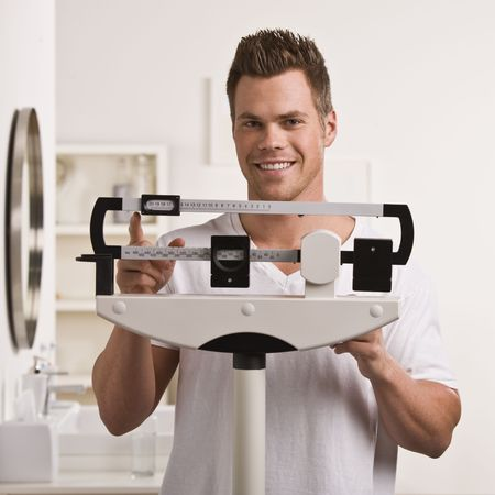 A young man is weighing himself on a bathroom scale.  He is smiling at the camera.  Square framed shot.