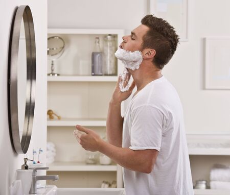 A man is shaving his face in the mirror.  He is looking away from the camera.  Horizontally framed shot. Stock Photo