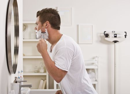 A young man is shaving his face in front of the bathroom mirror.  He is looking away from the camera.  Horizontally framed shot. Stock Photo