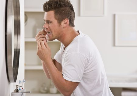 flossing: A young man is flossing his teeth in front of the bathroom mirror.  He is looking away from the camera.  Horizontally framed shot.