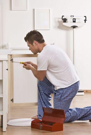 midlife: Attractive male kneeling and fixing cabinet door with screwdriver. Vertical