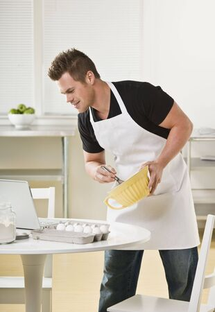 blue white kitchen: Attractive male cooking with mixing bowl and looking at laptop. Vertical Stock Photo
