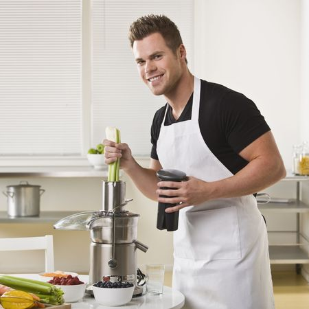 Attractive male with juicer, holding celery and smiling at camera. Square.