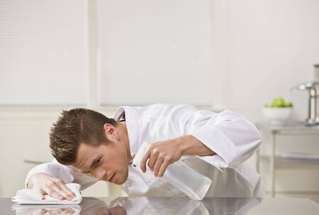 Attractive brunette male carefully cleaning table with cleaner. Horizontal. Stock Photo - 5333055