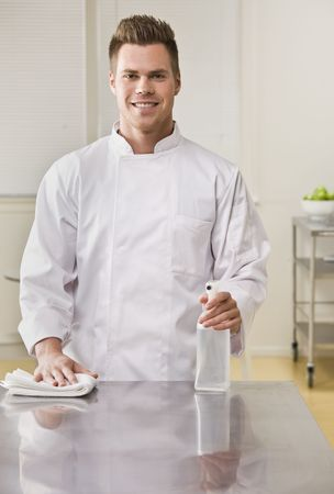 A young chef is cleaning the counter in a kitchen and smiling at the camera.  Vertically framed shot.