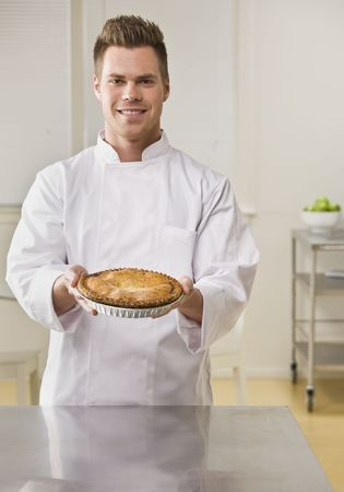 Attractive brunette male holding pie and smiling at camera. Vertical. photo