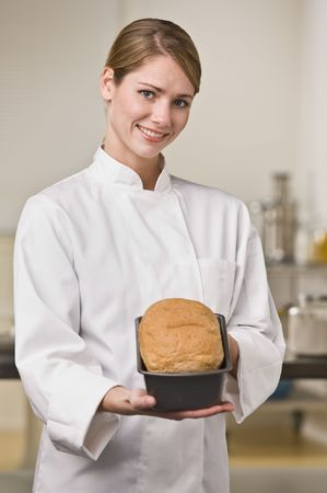 A young woman is standing in a kitchen and holding out a loaf of bread.  She is smiling at the camera.  Vertically framed shot. photo