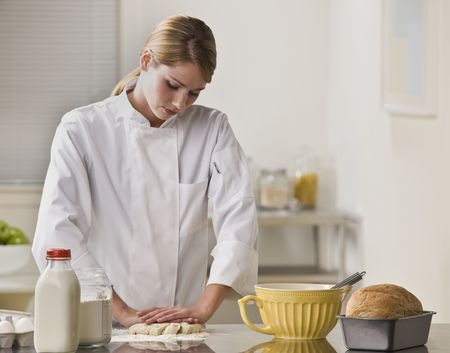 A woman is making a pie in her kitchen.  She is looking away from the camera. Stock Photo - 5333444