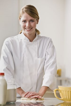 A female chef is kneading dough and smiling at the camera.  Vertically framed shot. photo