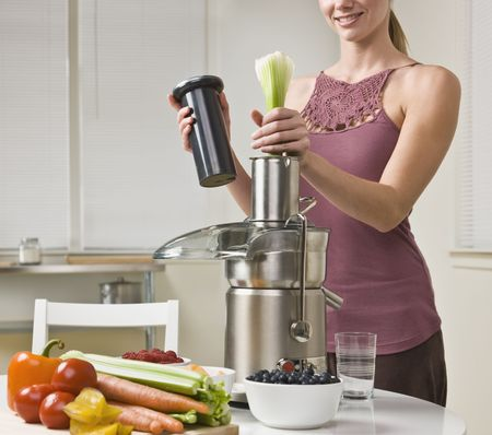 juicer: Attractive woman with juicer machine, adding celery and smiling. Horizontal.