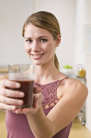 midlife: Blonde woman showing smoothie to the camera, smiling at camera. Vertical