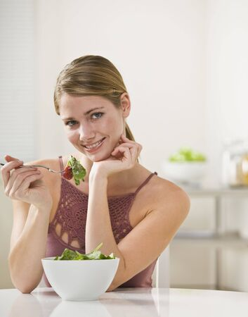 A young woman is eating salad and smiling at the camera.  Vertically framed shot. photo