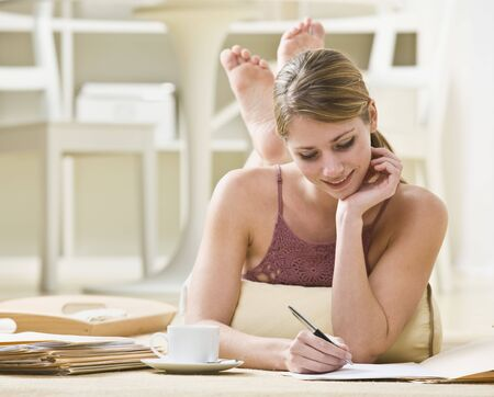 midlife: A young woman is laying on her stomach and working on paperwork.  She is looking away from the camera.  Horizontally framed shot.