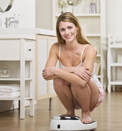 weighing: A young woman is crouching on a bathroom scale and checking her weight.  She is smiling at the camera.  Square framed shot. Stock Photo