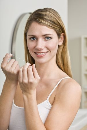 dental floss: A young woman is about to floss her teeth.  She is smiling at the camera.  Vertically framed shot.