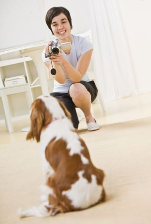 midlife: A young woman is taking a picture of her dog.  She is smiling and looking away from the camera.  Vertically framed shot. Stock Photo
