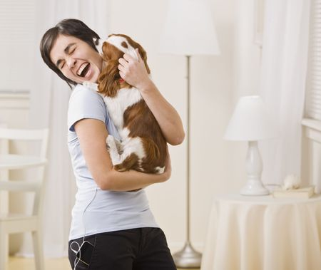 A woman is holding a puppy in her arms and laughing.  Horizontally framed shot.
