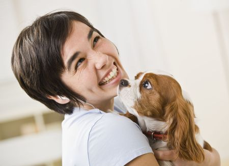 A woman is holding a puppy and smiling at the camera.  Horizontally framed shot. Stock Photo - 5333128