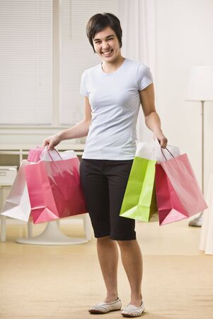 A young woman is holding multiple shopping bags and smiling at the camera.  Vertically framed shot. Stock Photo - 5333717
