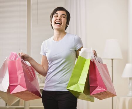 Woman with multi-colored shopping bags, smiling for the camera. Horizontal. Stock Photo - 5333423