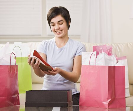 Cute brunette woman surrounded by shopping bags and looking at new shoes. Horizontal. Stock Photo - 5333202