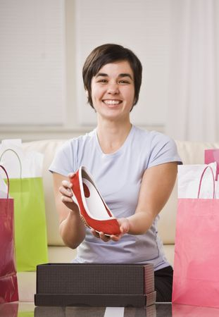 A young lady is holding up a shoe from a box and smiling at the camera.  She is surrounded by shopping bags.  Vertically framed shot. photo