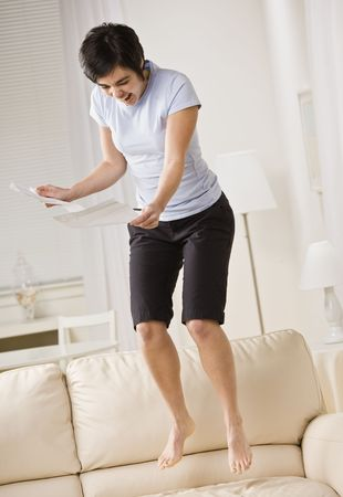 couch: An excited young woman is reading a piece of paper and jumping up and down on the couch.  She is looking away from the camera.  Vertically framed shot.