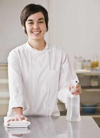 A woman is cleaning the counter in a kitchen.  She is smiling at the camera.  Vertically framed shot. photo