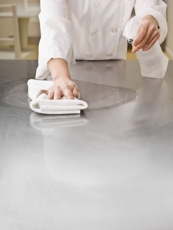 cleaning kitchen: A chef is cleaning a counter in a professional kitchen with a bottle of solution and a rag.  Vertically framed shot.