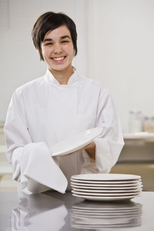 Smiling brunette woman drying dishes, smiling at camera. Vertical. photo
