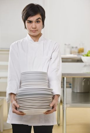 carrying: Brunette woman with questioning face, carrying heavy dishes and looking toward camera. Vertical