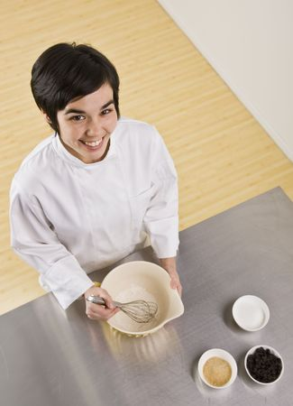 midlife: Attractive brunette woman with whisk and bowl, smiling at camera. Vertical