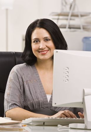 Attractive woman sitting at desk behind monitor typing on keyboard. Vertical Stock Photo