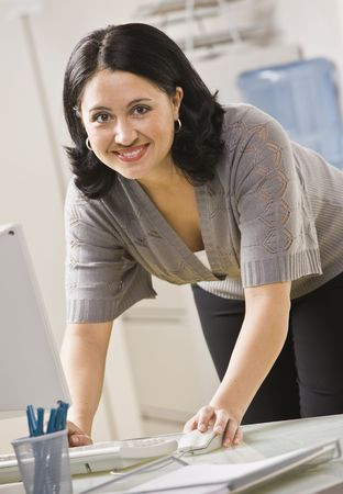A businesswoman is standing over a computer and smiling at the camera.  Vertically framed shot. Stock Photo - 5333451