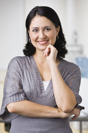 A young businesswoman is standing in an office and smiling at the camera.  Vertically framed shot. Stock Photo - 5333387