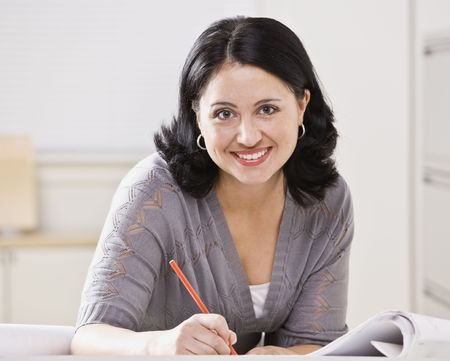 A beautiful Hispanic woman writing at a desk.  She is smiling at the camera.  Square compostion. Imagens