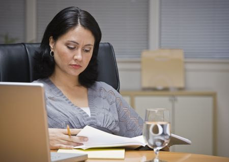 A young businesswoman is seated at a desk in an office.  She is looking away from the camera.  Horizontally framed shot. photo