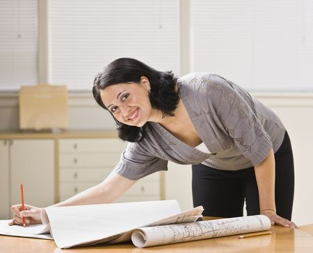 leaning over: Attractive woman leaning over desk with drawings. Pen in hand, looking at camera. Horizontal. Stock Photo