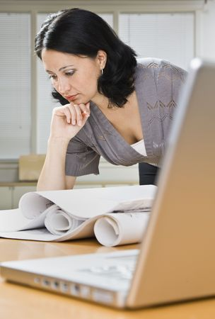 A young woman is leaning over a desk in an office and is looking at blueprints.  Vertically framed shot. Stock Photo