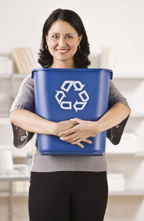 A businesswoman is holding a recycling basket and smiling at the camera.  Vertically framed shot. photo
