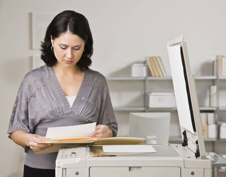 A businesswoman is making copies in an office.  She is looking away from the camera.  Horizontally framed shot.