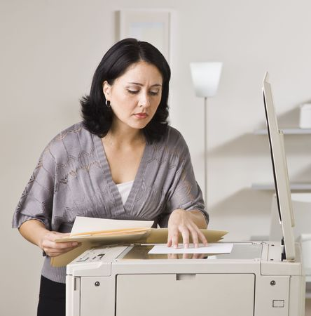 Attractive asian woman making copy on copy machine in office. Looking at paper on machine. Square.