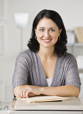 A young businesswoman is standing in an office and smiling at the camera.  Vertically framed shot. Stock Photo